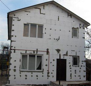Дом, зашитый пенопластом и подготовленный к отделочным работам