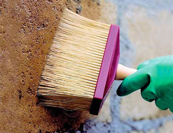 Грунтуем стену с помощью строительной кисти в два слоя.