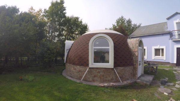 Купольный домик можно отделать камнем и гибкой черепицей