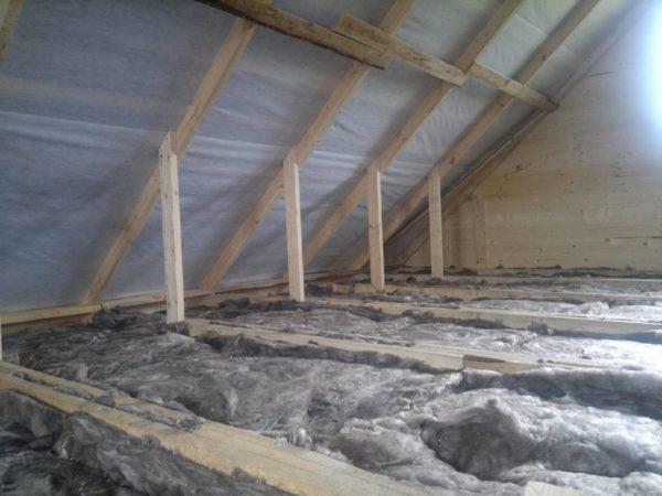 На этом фото минеральная вата низкой плотности уложена между балок деревянного перекрытия под холодной кровлей