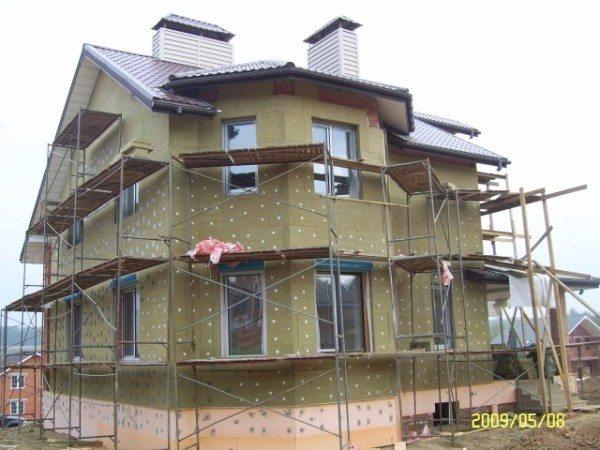 На фото - процесс утепления фасада минеральной ватой.