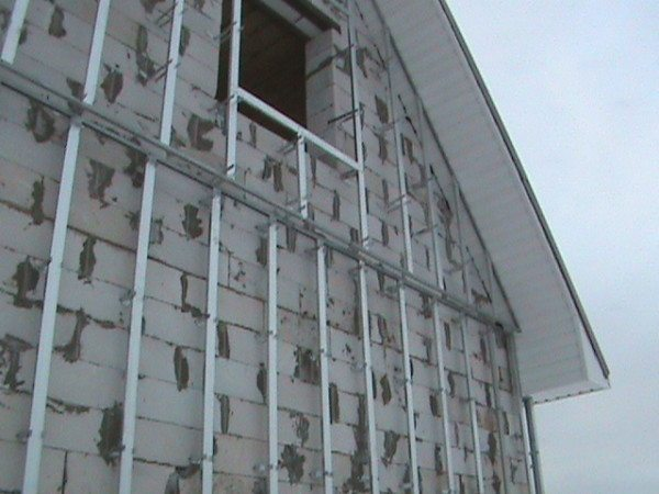 На фото – металлическая вертикальная обрешетка под сайдинг.
