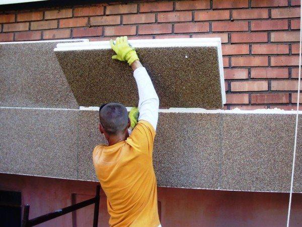 На фото – установка пенополистирольных фасадных плит на кирпичную стену