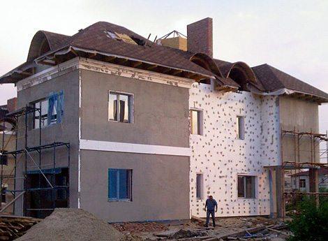 На фото дом, проводятся работы по утеплению