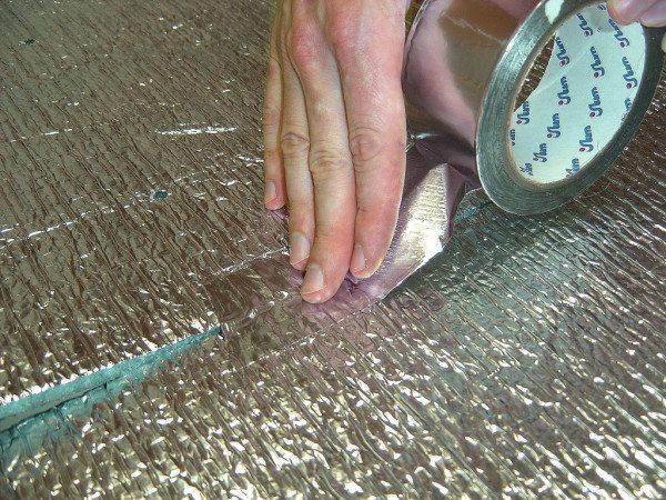 На фото показан процесс заделки стыков гидроизолятора при помощи металлического скотча.