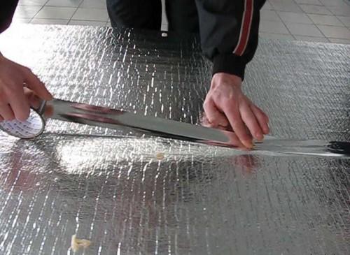 На фото полосы проклеиваются скотчем, чтобы предотвратить их смещение при укладке ламината.