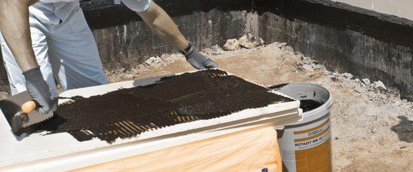 Нанесение полимерного клея на лист утеплителя.