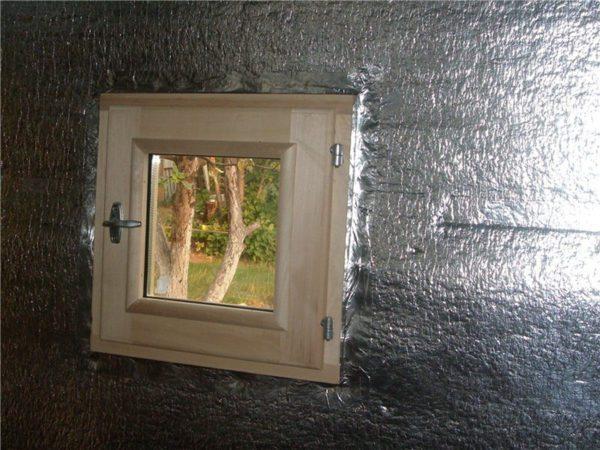 Небольшое деревянное окно в парилке. Стык со стеной проклеен фольгированной лентой