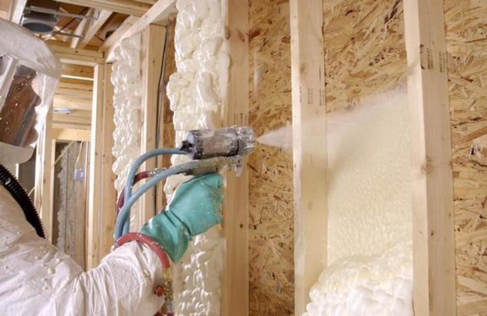 Обработка стены жидким пенополиуретаном с использованием распылителя и костюма химзащиты.