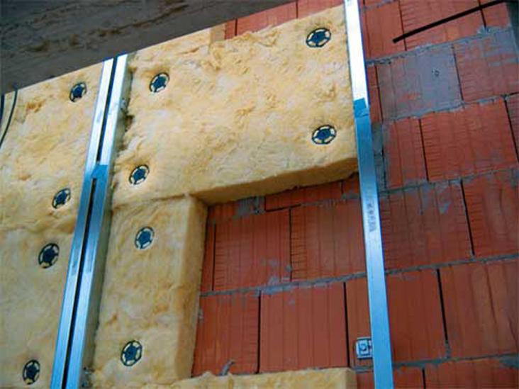 Пазы металлопрофилей словно созданы для панелей минеральной ваты для стен, необходимо только правильно подобрать толщину. Способ же крепления может быть любой. На фото использовать такие надёжные дюбеля позволяет предварительно подготовленная стена