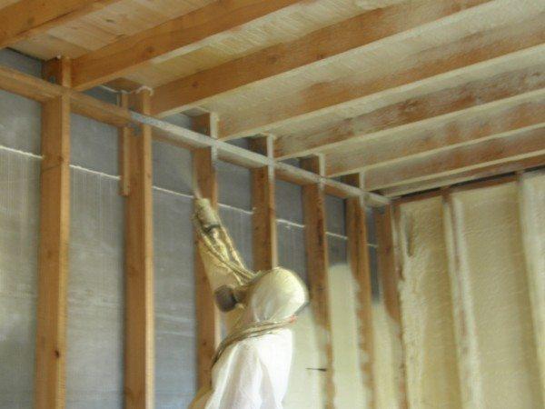 Процесс нанесение пенополиуретана на стену каркасного дома.