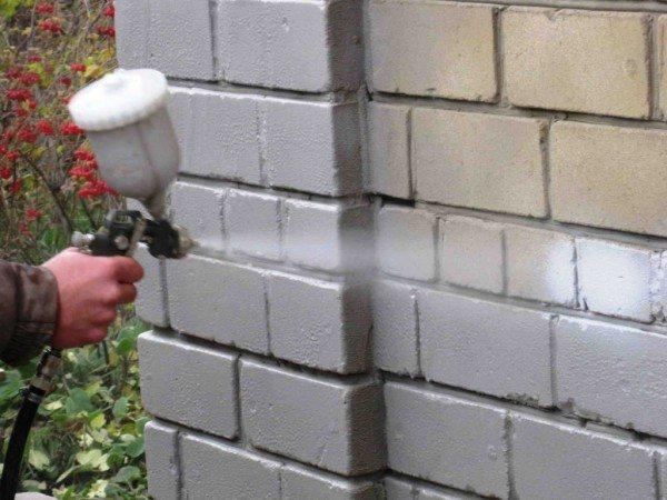 Процесс нанесения жидкой керамики на стену частного дома путем напыления из пульверизатора.