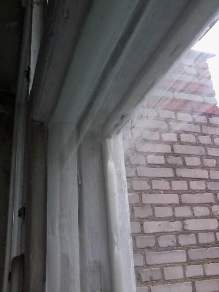 Старое деревянное окно с примитивным изолятором из поролона