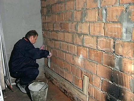 Стену очищаем и шпаклюем трещины.