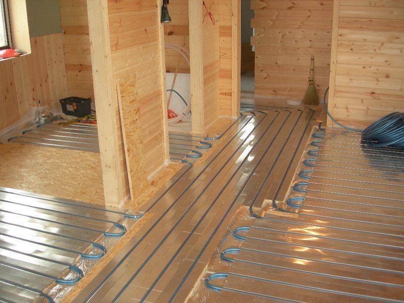 В бревенчатом или каркасном доме из дерева тоже можно уложить теплый пол водяного типа. Но придется учесть ряд неочевидных нюансов!