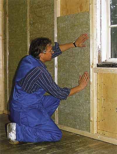 Внутренняя теплоизоляция квартиры. На фото показана укладка утеплителя между брусьев деревянной обрешетки.
